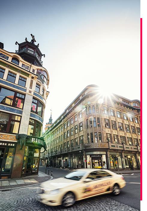 Taxi fährt an zwei mehrstöckigen Gebäuden in Leipzig vorbei.