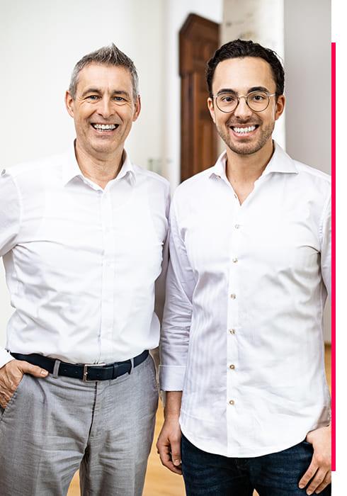 Geschäftsführer Maximilian Wöber von Wöber Immobilien, lächelt im Büro mit seinem Vater in die Kamera.