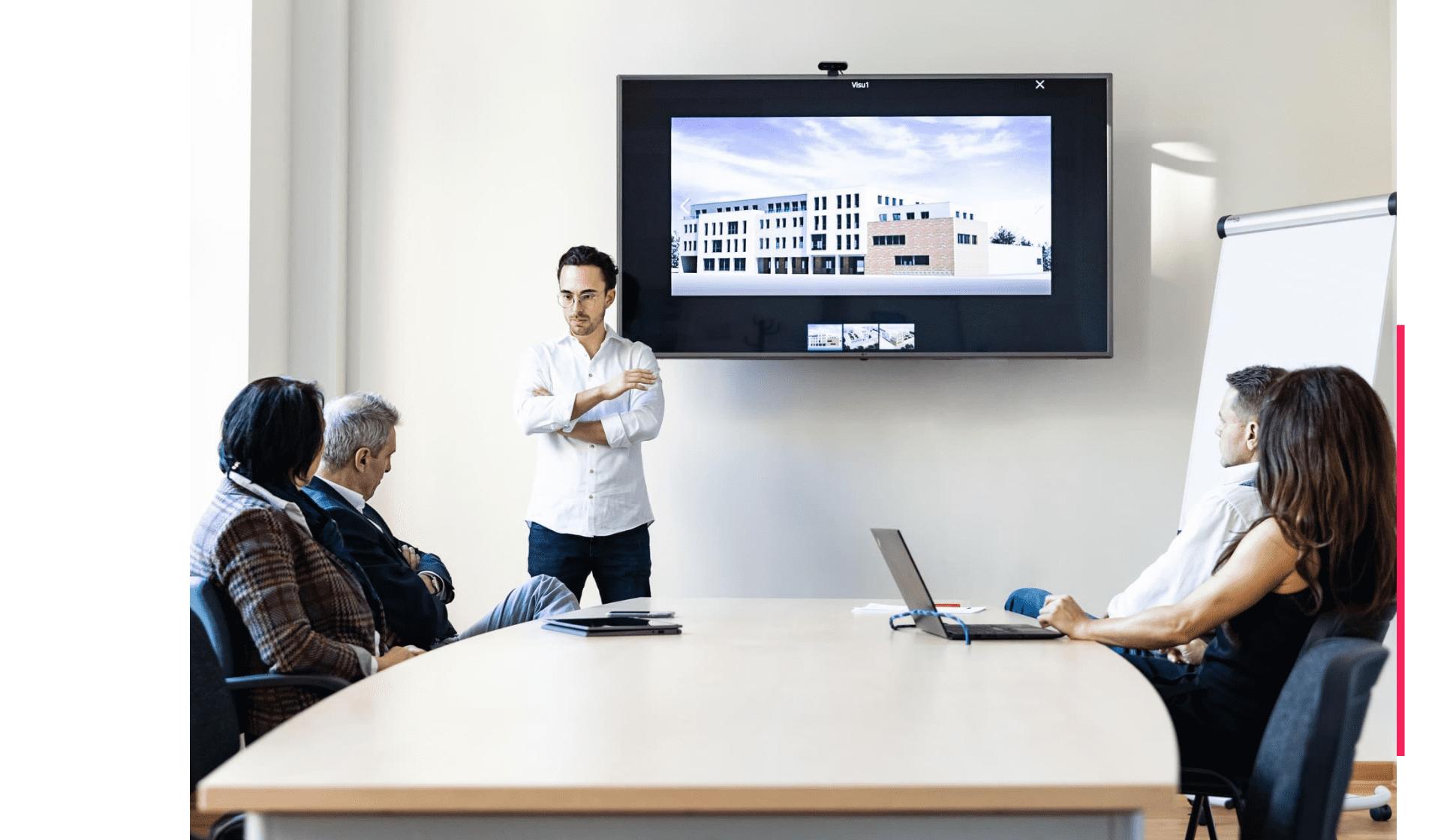 Das Team von Wöber Immobilien präsentiert eine Neubauimmobilie in einem Meeting Raum.